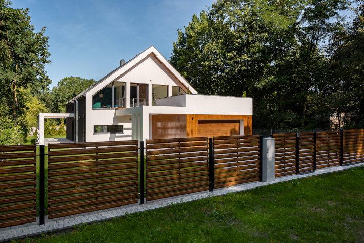 Dom jednorodzinny z estetycznym, drewnianym ogrodzeniem.