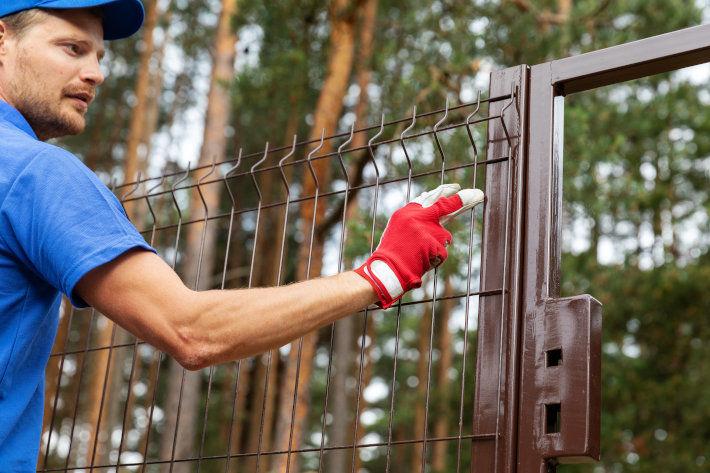 Pracownik montujący ogrodzenie stalowe.