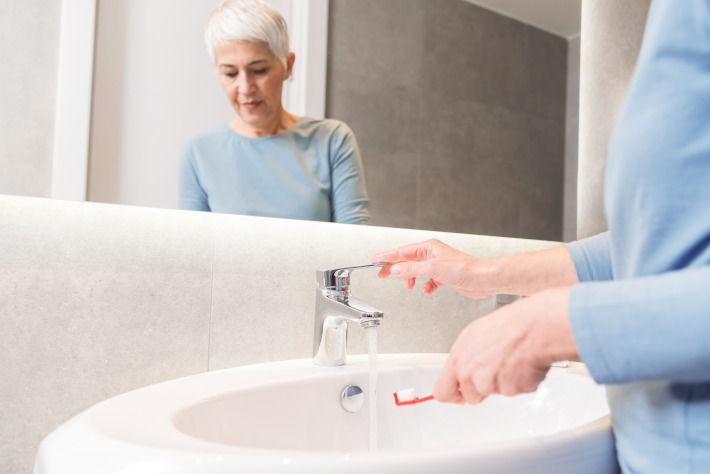 Emerytka przy zlewie w łazience