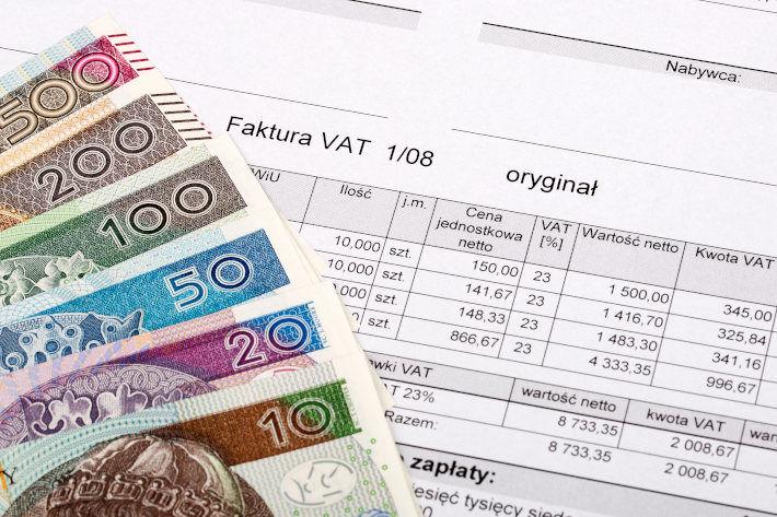 Banknoty o różnych nominałach rozłożone na fakturze vat