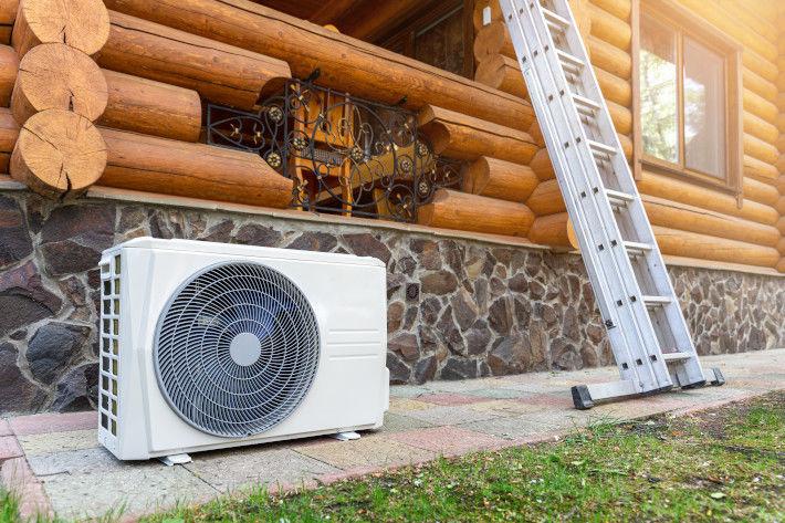 Pompa ciepła przed drewnianym domkiem