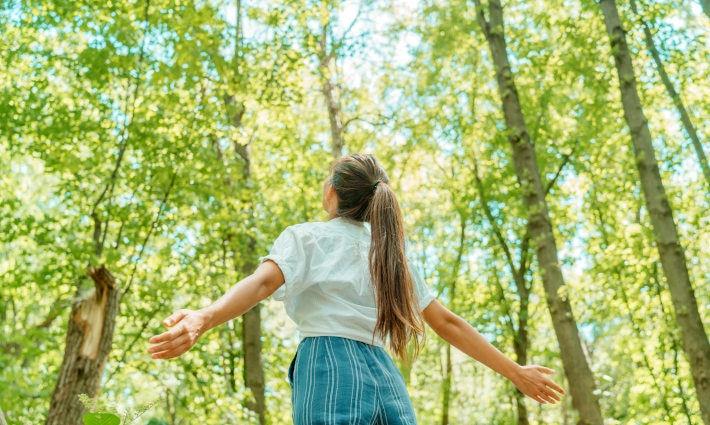 Młoda kobieta w lesie spogląda na zielone korony drzew