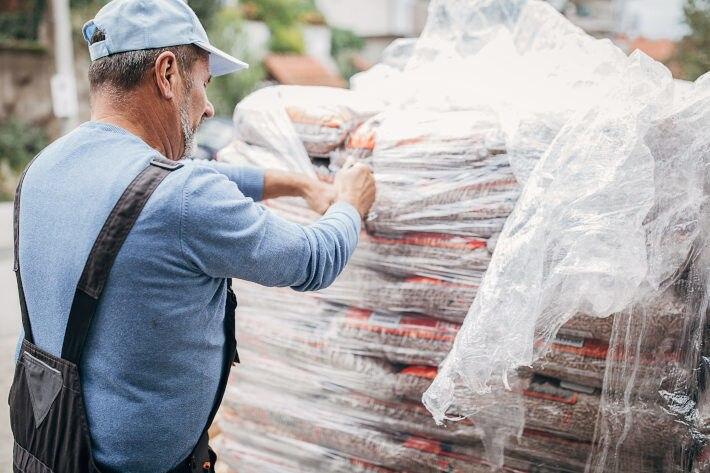 Mężczyzna rozrywający folię, w którą zapakowana jest duża ilość paletek opałowych