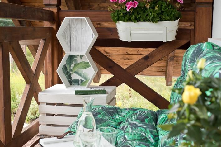 Białe półki sześciokątne stojące na stoliku z białej, drewnianej skrzynki na balkonie