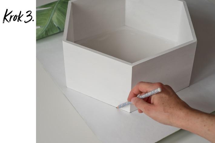 Odrysowywanie ołówkiem białej, sześciokątnej półki na tylnej części tapety ściennej